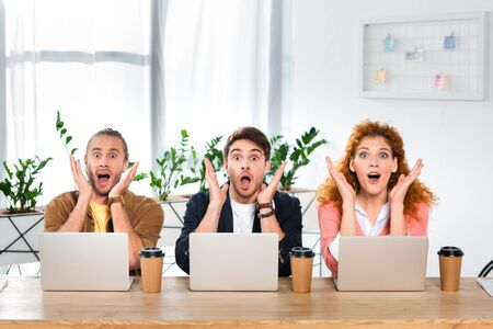 three shocked friends sitting at table and looking at camera Imagens