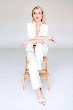 smiling beautiful young blonde woman in total white outfit sitting on chair Banque d'images