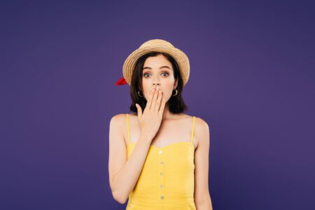 shocked girl in straw hat covering mouth with hand isolated on purple