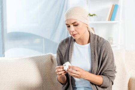 sick woman with head scarf holding tissue while sitting on sofa