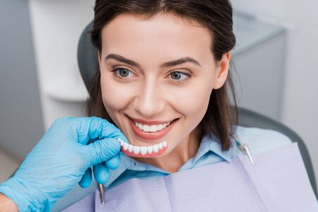 cropped view of dentist holding prosthesis near happy girl in dental clinic 写真素材