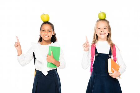 two cheerful multicultural schoolgirls with apples on heads showing idea gestures isolated on white 写真素材 - 131881363