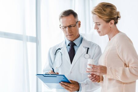 doctor in glasses holding clipboard with pen near woman with bottle