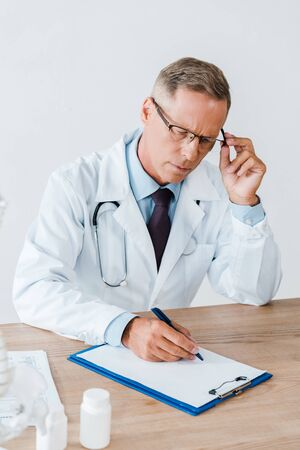 doctor in white coat touching glasses and writing diagnosis in clinic