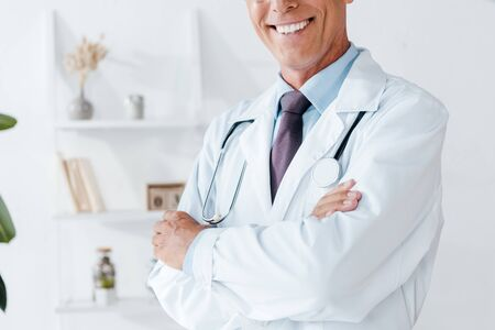 cropped view of happy doctor in white coat with crossed arms