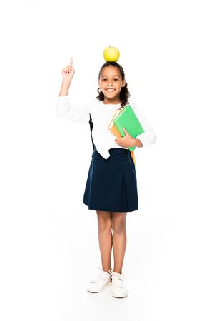 full length view of african american schoolgirl with apple on head holding books and showing idea gesture on white background