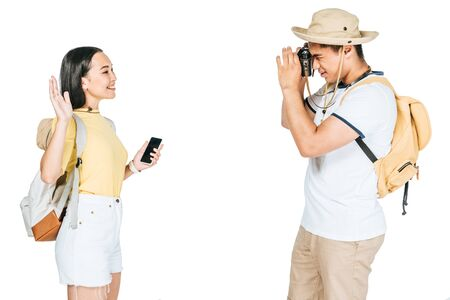young asian tourists taking photo of girlfriend waving hand isolated on white