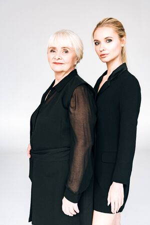 elegant blonde granddaughter and grandmother in total black outfits isolated on grey