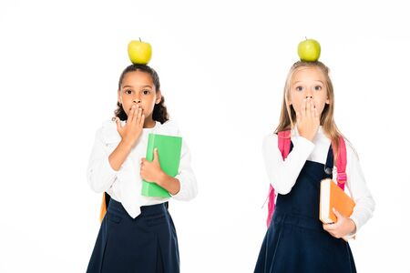 two shocked multicultural schoolgirls with apples on heads covering mouths with hands isolated on white 写真素材 - 131881580