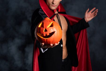 cropped view of man holding halloween pumpkin and gesturing on black with smoke  Stok Fotoğraf