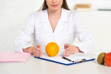 partial view of dietitian in white coat with fruits and vegetable at workplace 写真素材