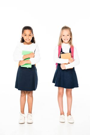 full length view of two adorable multicultural schoolgirls holding books on white background 写真素材 - 131881693