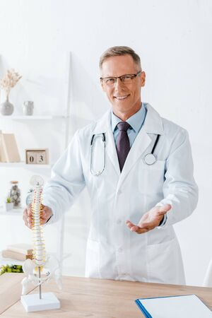 cheerful doctor in glasses and white coat touching spine model 写真素材