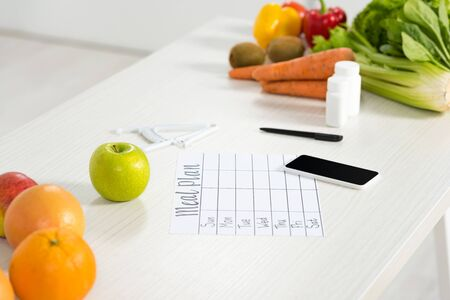 meal plan, smartphone with blank screen, pills, pen, caliper, fresh fruits and vegetables on table