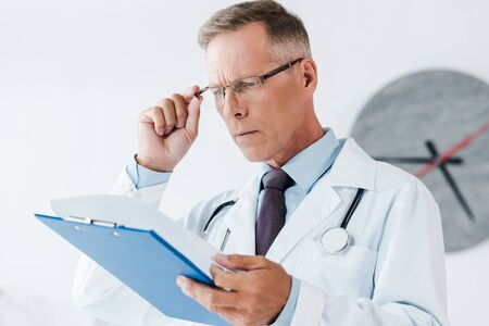 selective focus of handsome doctor in white coat looking at clipboard and touching glasses in hospital 写真素材