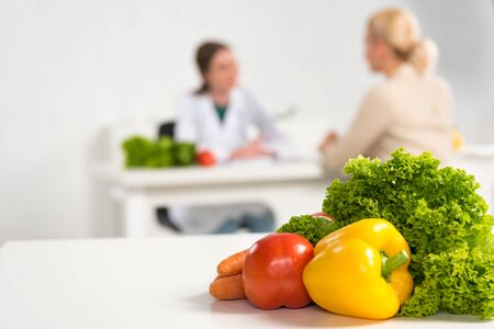 selective focus of dietitian in white coat and patient at table and fresh vegetables on foreground
