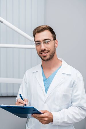 handsome bearded doctor in glasses holding clipboard in clinic