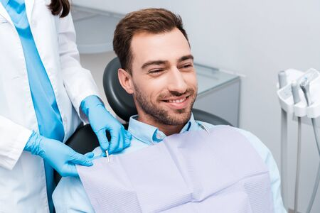 cropped view of dentist in blue latex gloves standing near cheerful patient 写真素材