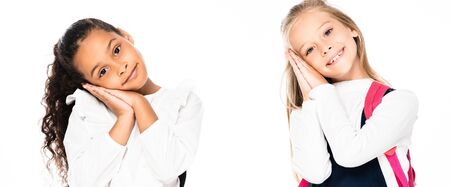 panoramic shot of two tired multicultural schoolgirls smiling at camera isolated on white