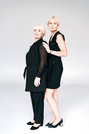 full length view of elegant blonde mature daughter and senior mother in total black outfits isolated on grey