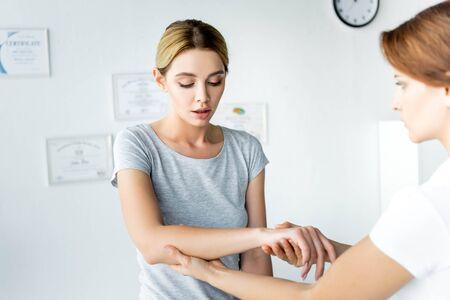 selective focus of chiropractor touching hand of attractive patient in grey t-shirt 写真素材