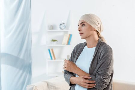 sick and sad woman with head scarf standing in living room
