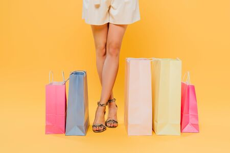 cropped view of woman with crossed legs near shopping bags isolated on yellow