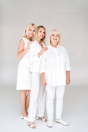 full length view of three generation smiling blonde women on grey Imagens