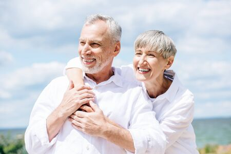 Happy senior couple en chemises blanches embrassant sous ciel bleu Banque d'images