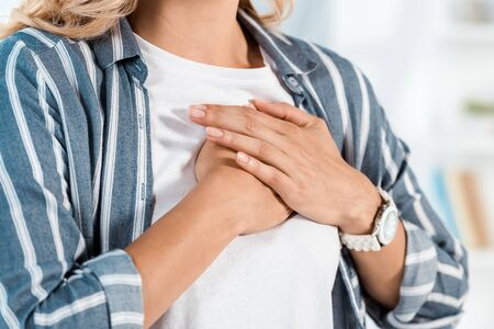 cropped view of woman touching chest at home
