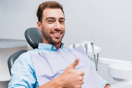 happy bearded man smiling while showing thumb up in dental clinic
