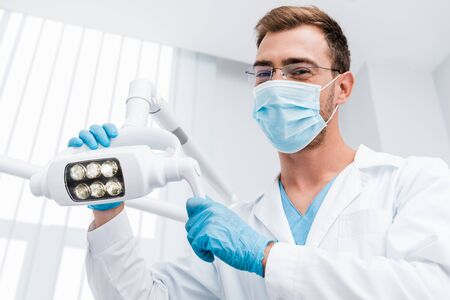 low angle view of dentist in glasses and medical mask touching medical lamp and looking at camera 写真素材