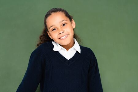 cheerful african american schoolgirl shrugging while standing near green chalkboard and smiling at camera Stock Photo