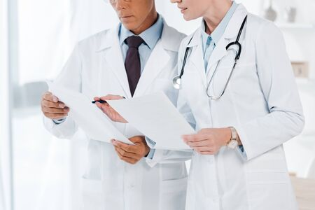 cropped view of doctors holding blank papers in clinic
