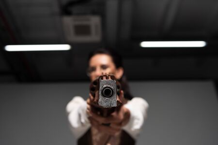 selective focus of confident steampunk woman aiming with pistol at camera Stock Photo