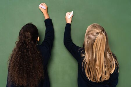 back view of two multicultural schoolgirls writing on chalkboard with chalks 写真素材 - 131881987