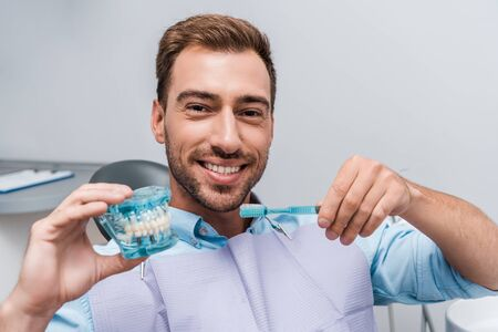 happy man holding tooth model and toothbrush in clinic 写真素材