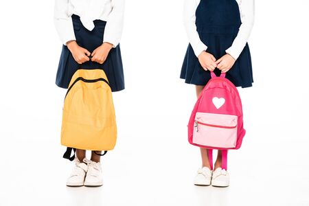 cropped view of two multicultural schoolgirls holding backpacks on white background 写真素材 - 131881928