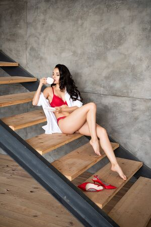 sexy girl in red underwear and white shirt sitting on stairs, drinking coffee with closed eyes
