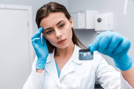 selective focus of pensive and attractive dentist looking at x-ray