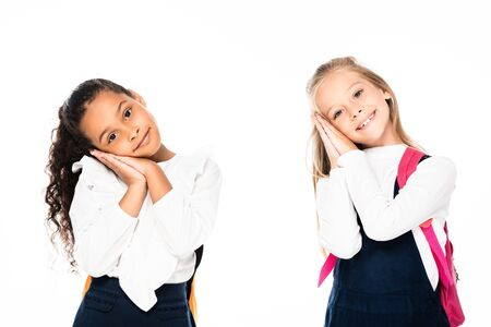 two smiling, tired multicultural schoolgirls looking at camera isolated on white