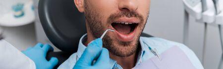 panoramic shot of dentist holding dental instrument near man 写真素材