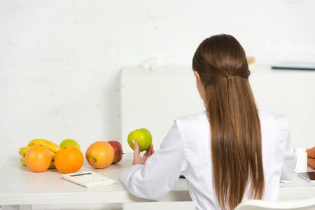 back view of dietitian in white coat holding green apple at workplace