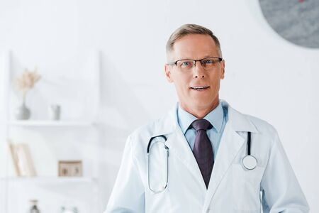 handsome doctor in glasses looking at camera in hospital 写真素材