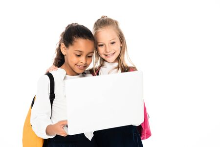 two cheerful multicultural schoolgirls smiling while using laptop isolated on white 写真素材