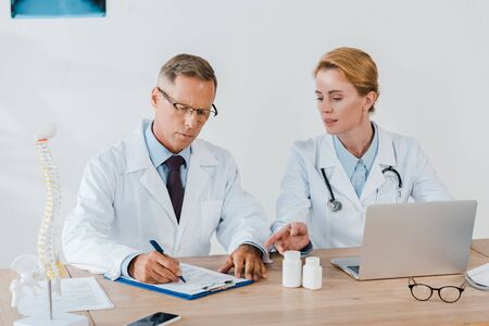 attractive doctor pointing with finger near laptop and coworker in glasses writing diagnosis 写真素材