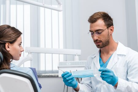 selective focus of handsome man in glasses holding medical mask near attractive patient