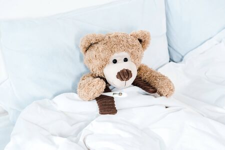 teddy bear on bed with white bedding and pillows