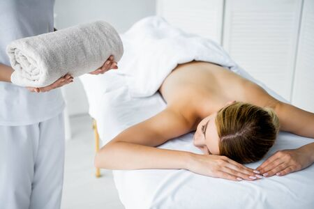 cropped view of masseur holding towel and woman lying on massage mat