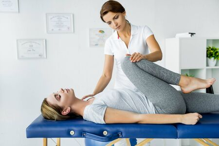 chiropractor touching leg of attractive patient in grey t-shirt
